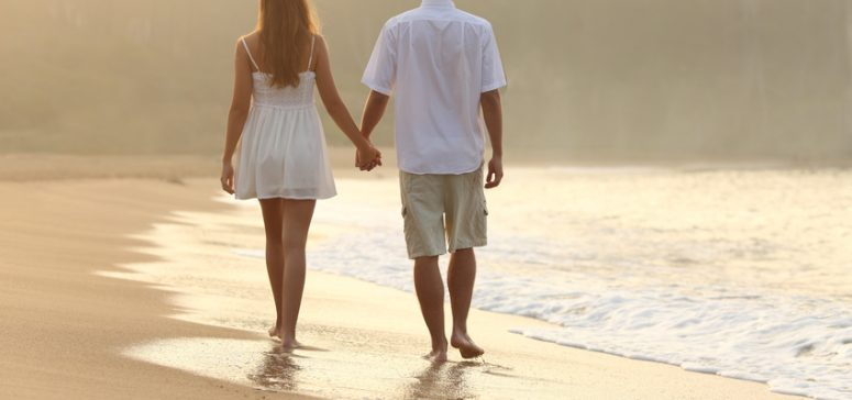 Back view of a couple walking and holding hands on the sand of a beach at sunset